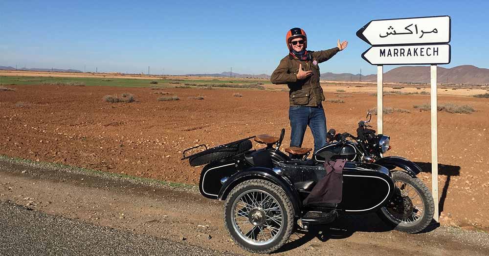 Homme début sur un sidecar pointant un panneau Marrakech