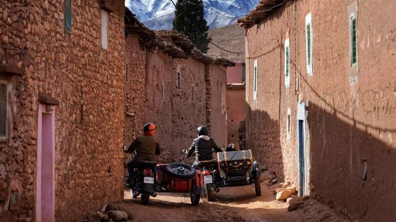 Two sidecars driving in between stone houses in the Atlas Mountains next to Marrakech